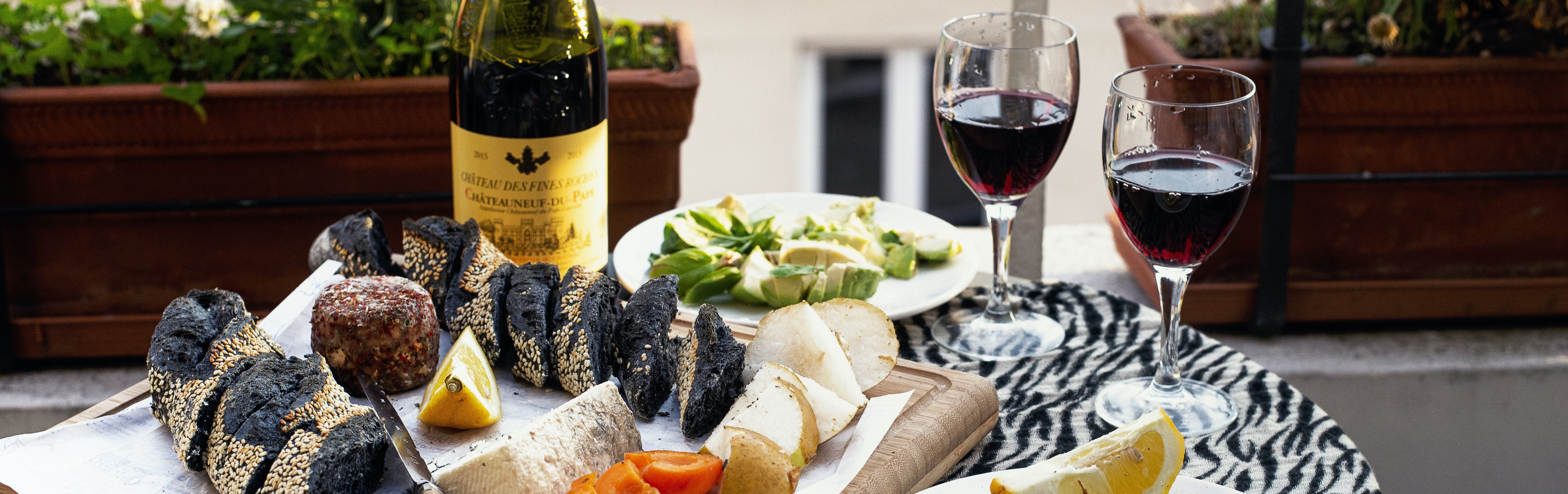 a-cheese-board-and-wine-on-a-balcony-at-sunset